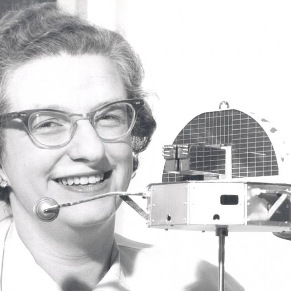Nancy Grace Roman holds a model of the Orbiting Solar Observatory.