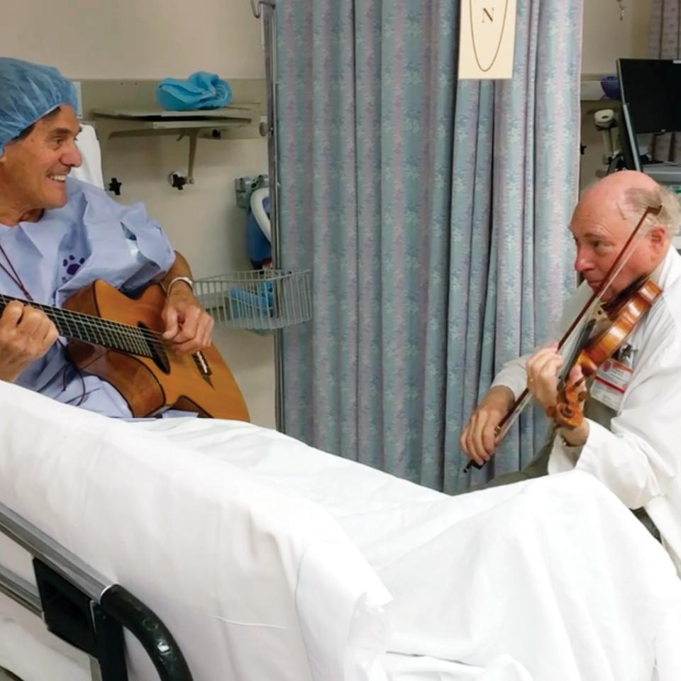 William Sloan and a patient playing a song before surgery