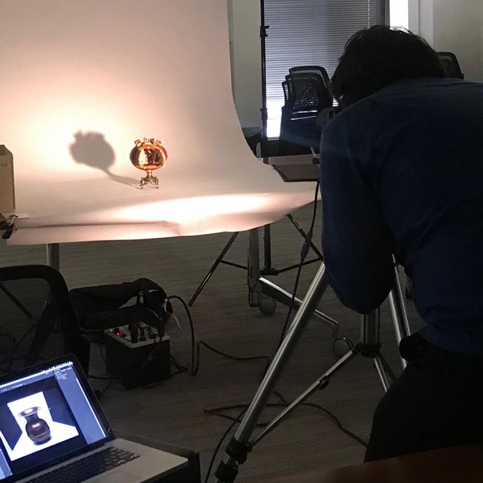 Photographer Nathan Keay photographing a decorated egg from the Special Collections Research Center