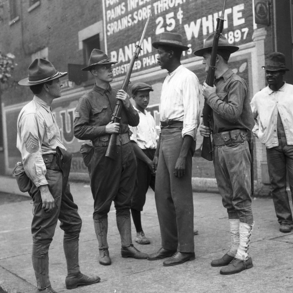 National Guard soldiers and African American men on a street corner in Chicago during the 1919 race riot