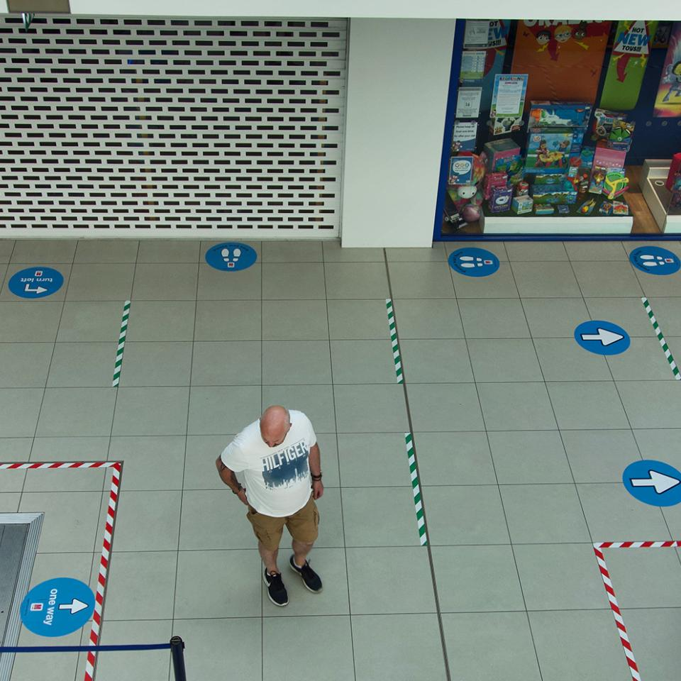 Interior of a shopping mall with one person marked with social distancing stickers